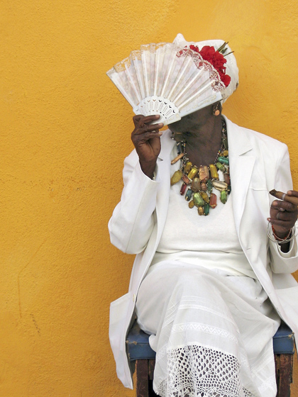 Lady holding a fan and a cigar dressed in white
